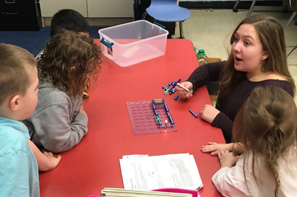 Photograph of volunteer teaching kindergartners about circuits and engineering