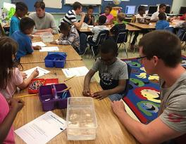 Photograph of second graders learning about the scientific method and working on building their clay boats.
