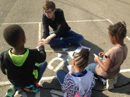 Photograph of WOW volunteer talking to first graders about aerodynamics and airplanes for one of our scientific method experiments.