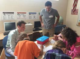 Photograph of Battelle employee/ WOW volunteers talking to 5th graders about mystery boxes and the scientific method.