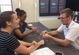 Photograph of WOW student volunteers building a spaghetti-marshmallow tower