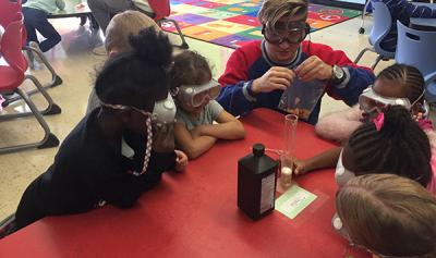 Photograph of WOW volunteer teaching kindergartners about the physical reaction between hydrogen peroxide and potatoes.