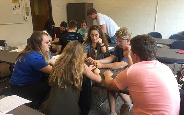 Photograph of WOW student volunteers attending a training and trying to build a spaghetti-marshmallow tower