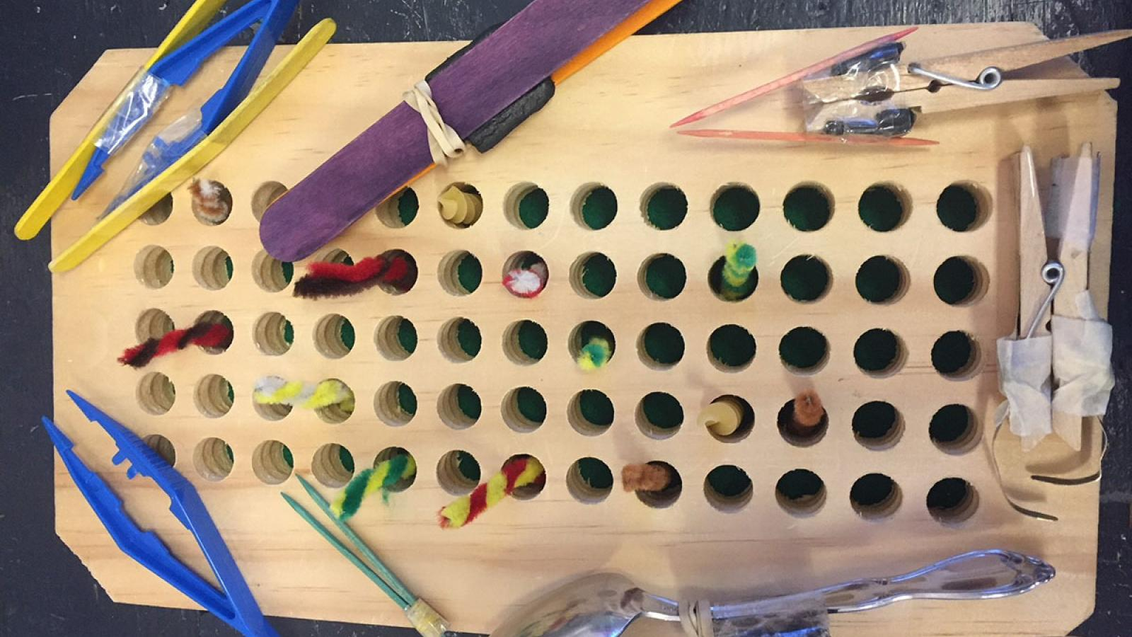 Photograph of a birds and beaks experiment where students use various made beaks (using spoons, toothpicks, tweezers) and try to pick up the most worms (made of pipe cleaners twisted together and raw pasta)
