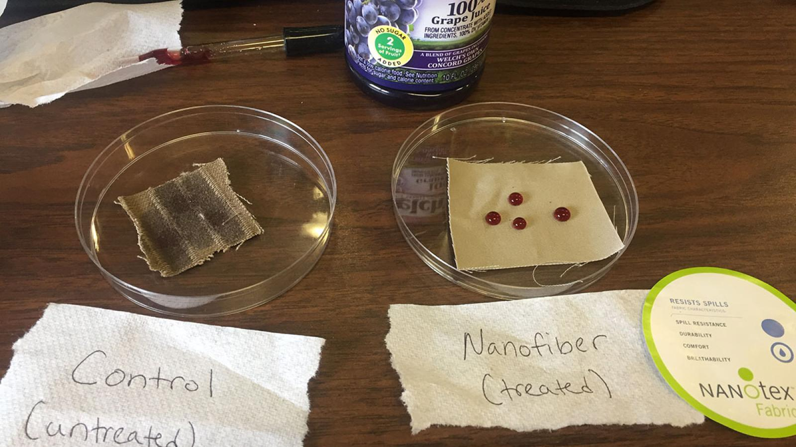 Photograph of a nanochemistry experiment showing untreated fabric vs. nanofiber fabric. The untreated fabric has the grape juice soaking in whereas the nanofiber fabric has droplets of grape juice and it is not sinking in.