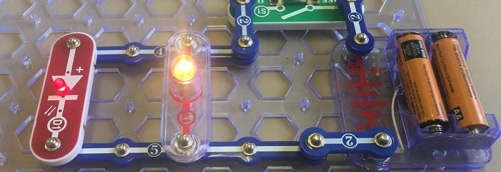 Photograph of a closed parallel circuit created using snap circuits, an LED diode, light bulb, switch, and batteries.